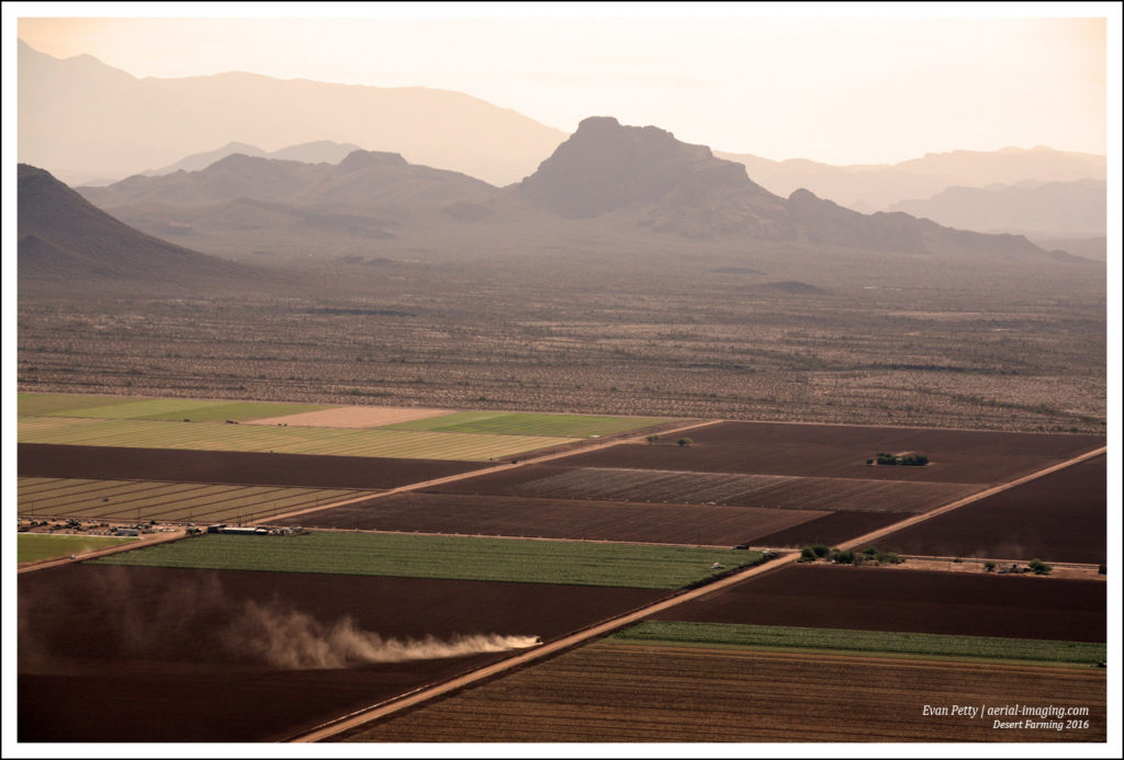 An Aerial View of A Farmer With A Dust Cloud